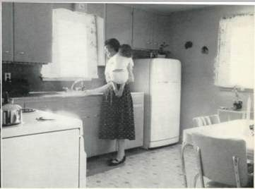 Mother and infant daughter by kitchen sink, circa 1950s